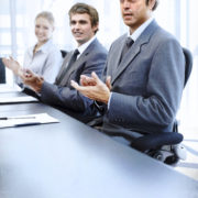 kaiserkom | Successful applauding executives sitting at the table